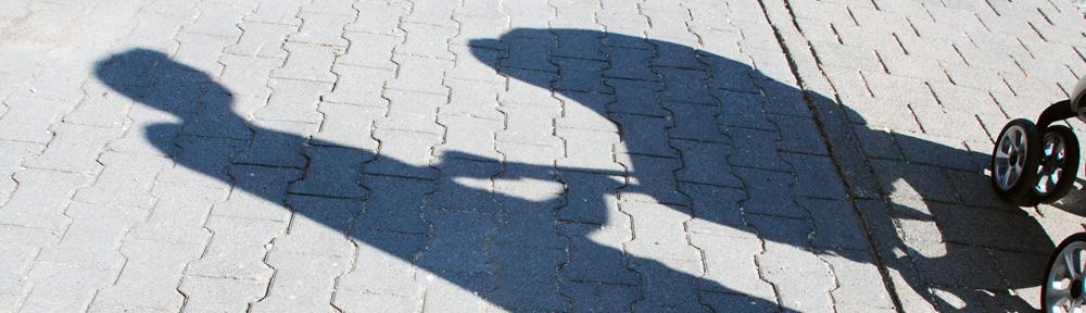 Schatten eines Mannes der einen Kinderwagen schiebt