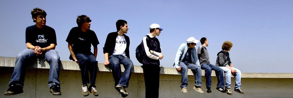 Männliche Jugendliche sitzen auf einer Mauer