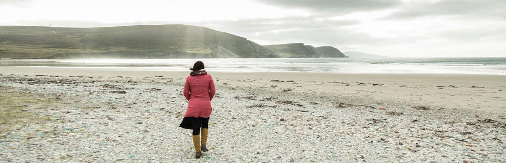 Eine Frau geht am Meer spazieren