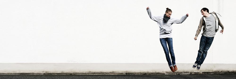 Eine Frau und ein Mann springen vor Freude in die Luft