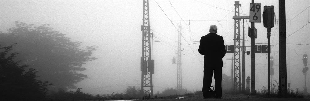 Ein Mann am Bahnhof im Nebel