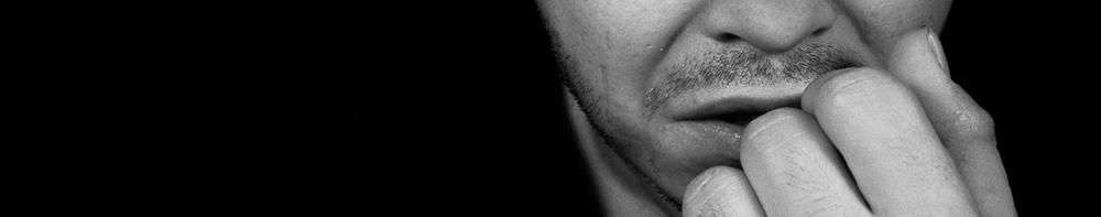 Mann hält sich den Handrücken vor den Mund