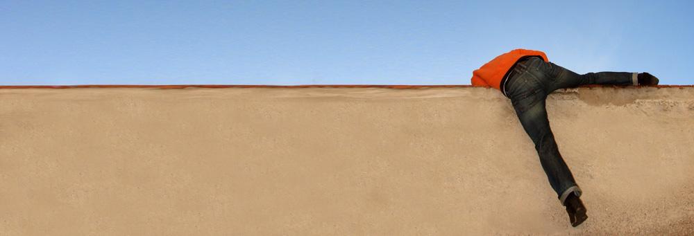 Mann klettert über eine Mauer