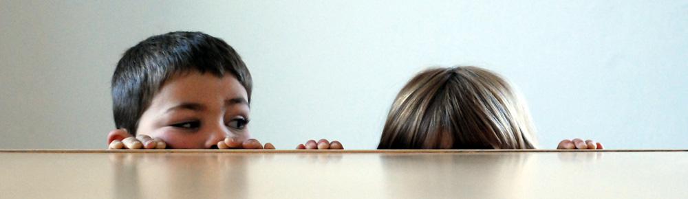 Junge guckt über die Tischkante