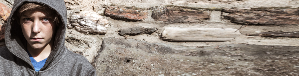 Junge in Kapuzenpullover vor Steinwand