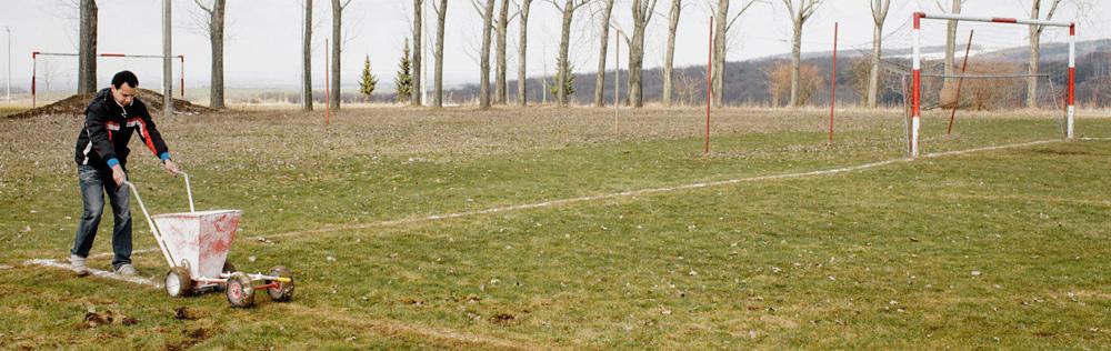 Ein Platzwart frischt die Linien eines Fußballfeldes auf