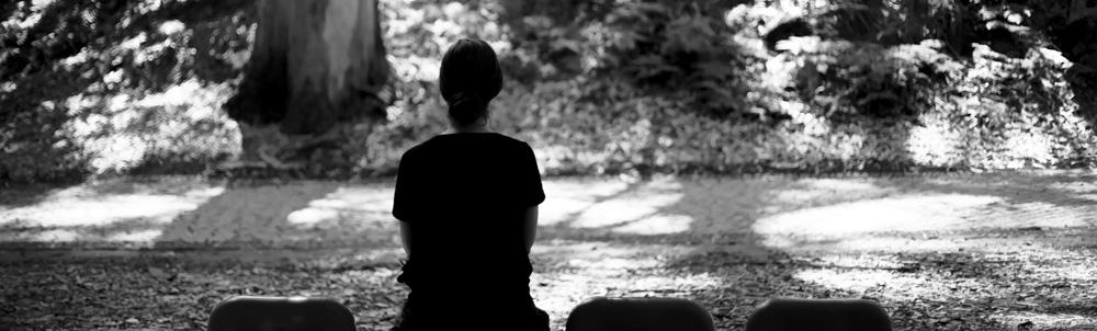 Eine Frau sitzt auf einer Parkbank