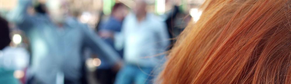 Eine rothaarige Frau schaut auf eine Gruppe von Männern