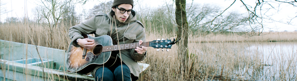 Ein junger Mann spielt Gitarre an einem See