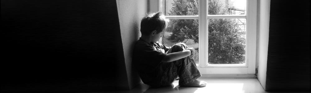 Ein Junge sitzt am Fenster
