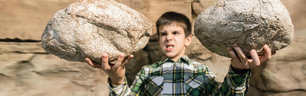 Junge hält zwei große Steine in den Händen