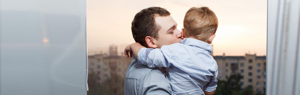 Ein Vater küsst seinen Sohn im Abendlicht