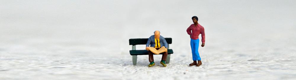 Ein weißer Mann liest Zeitung auf einer Parkbank, ein farbiger Mann steht daneben