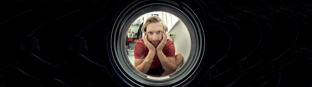Mann schaut in eine Waschmaschine