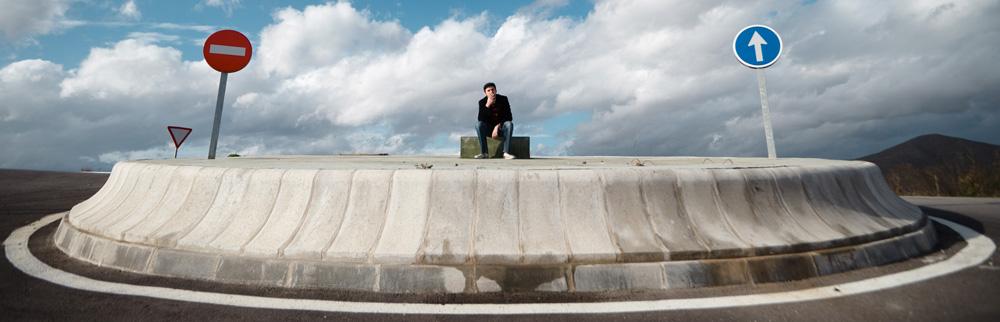 Ein Mann sitzt auf einer Verkehrsinsel