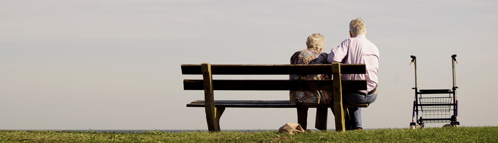 Ein Mann und eine Frau sitzen auf einer Parkbank neben einem Rollstuhl