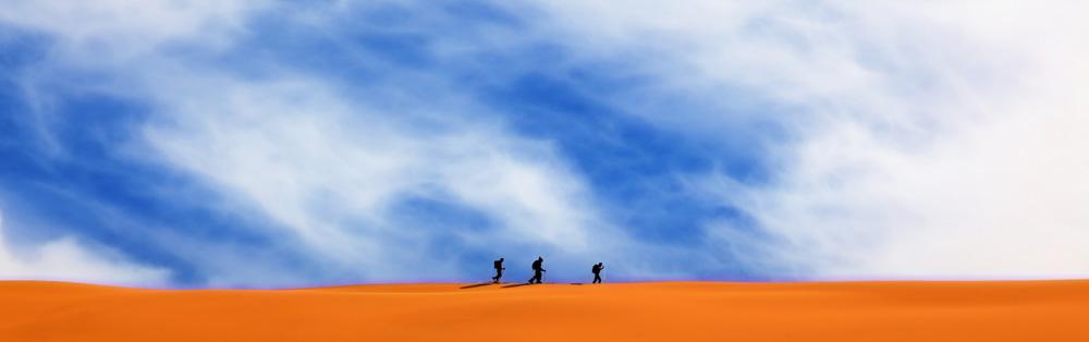 Drei Männer auf einer Sanddüne in Marokko
