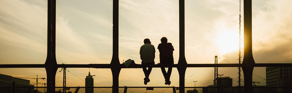 Zwei Männer sitzen auf einem Brückengeländer