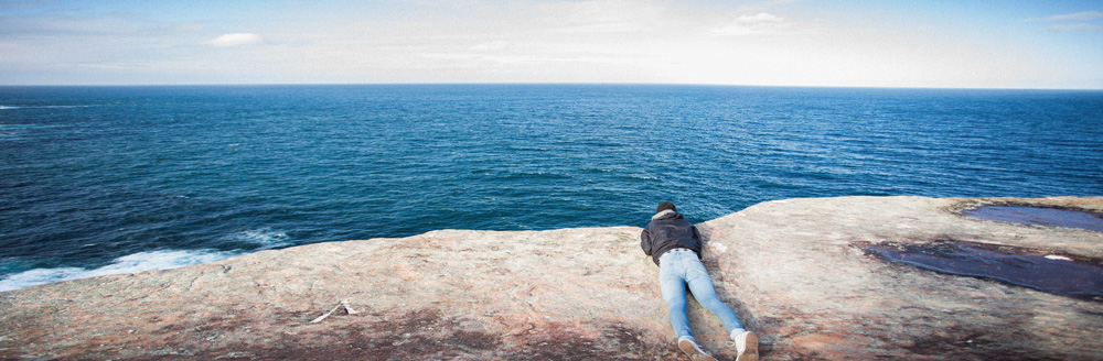 Mann schaut liegend über einen Felsen aufs Meer