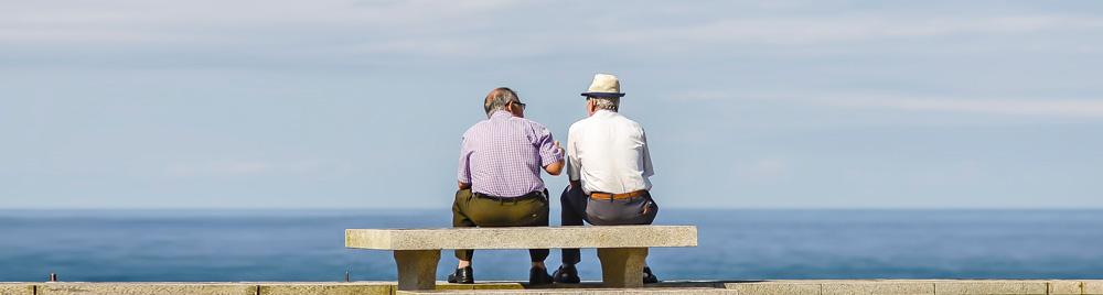 Zwei Männer sitzen auf einer Bank am Meer