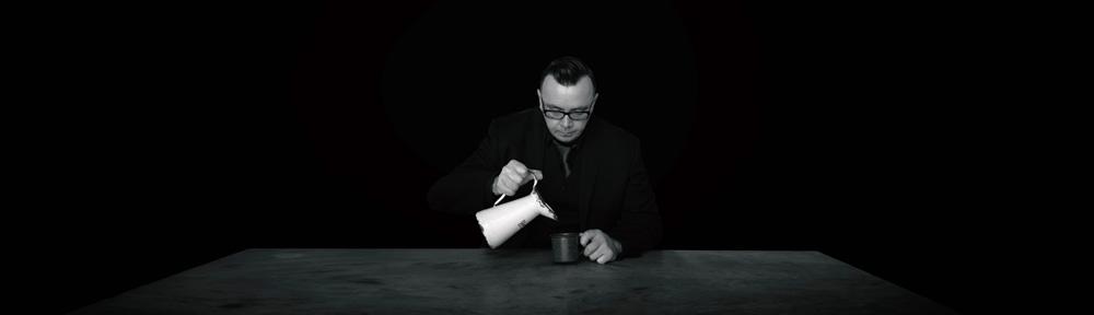Ein Mann sitz am Tisch und gießt sich ein Getränk ein