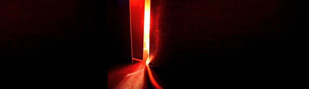 Rotes Licht scheint durch eine offene Tür