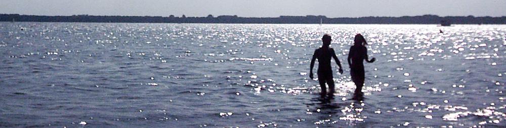 Zwei Menschen gehen zum Baden in einen See