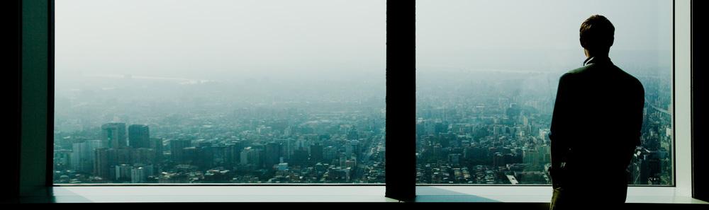 Ein Mann steht am Fenster eines Hochhauses