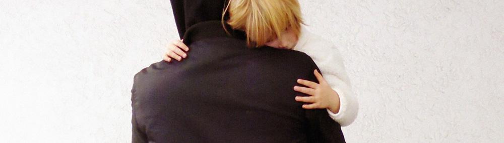 Ein Mann trägt ein Kind auf dem Arm