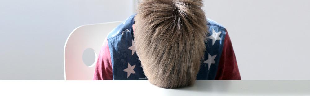 Ein Junge stützt seinen Kopf auf einen Tisch