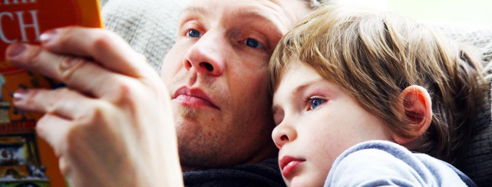 Vater und Sohn betrachten ein Bilderbuch