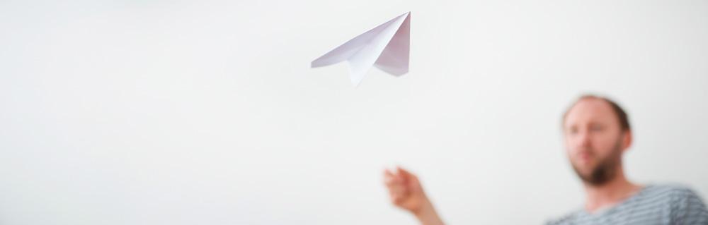 Ein Mann wirft ein Papierflugzeug