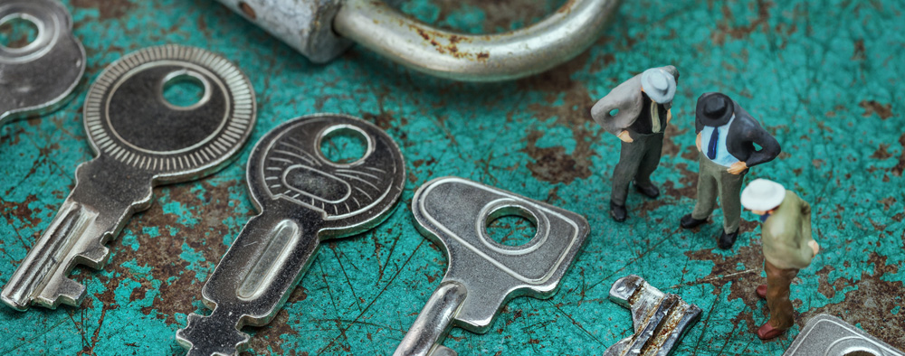 Drei Männer stehen um einige Schlüssel herum