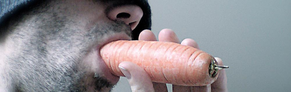 Ein Mann isst eine Möhre