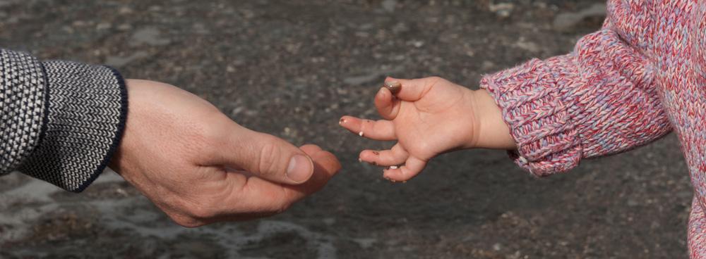 Ein Kind zeigt einem Erwachsenen einen Stein