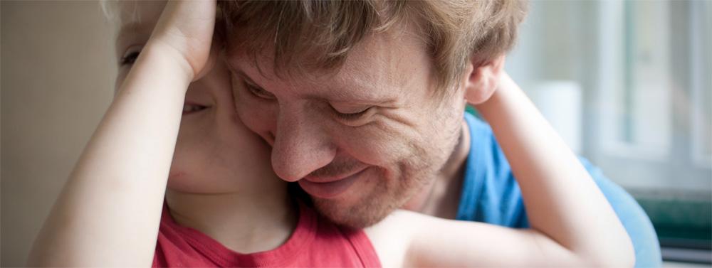 Ein Vater kuschelt mit seinem Sohn