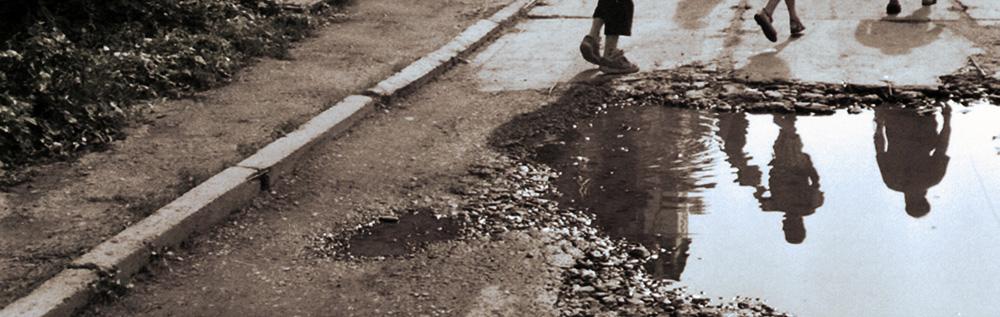 Fußgänger spiegeln sich in einer Pfütze