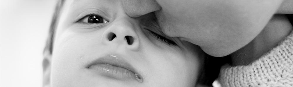 Ein Junge wird von seiner Mutter geküsst