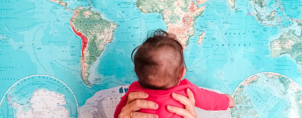 Vater hält Tochter vor eine Weltkarte