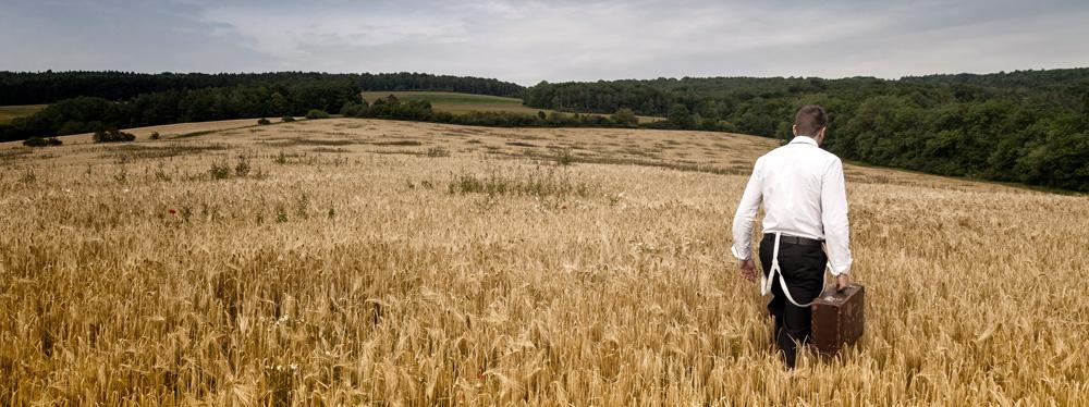 Ein Mann mit einem Koffer geht durch ein Kornfeld