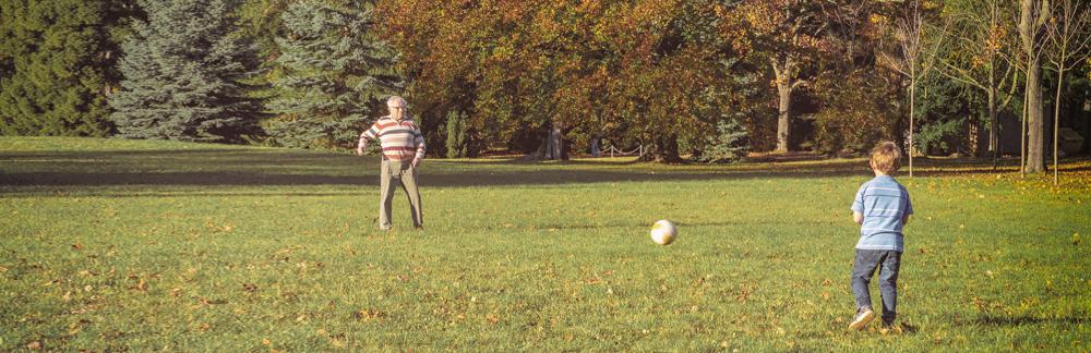 Opa und Enkel spielen Fußball auf einer Wiese