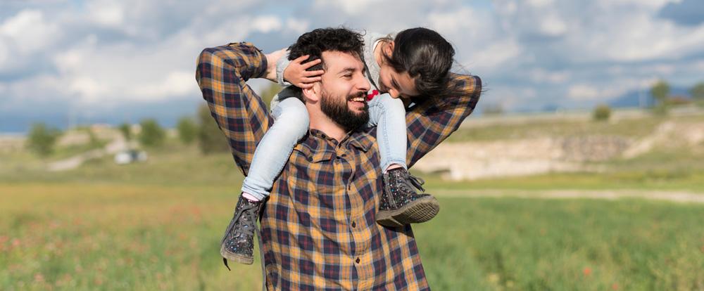 Ein Vater trägt seine Tochter auf seinen Schultern
