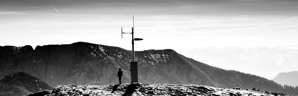 Ein Junge auf einem Berg schaut zum Himmel