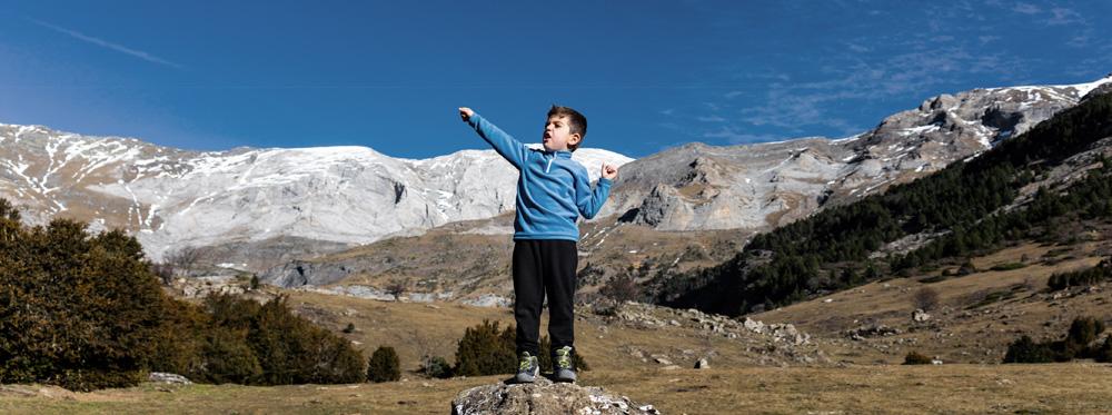 Junge auf einem Felsen in den Bergen