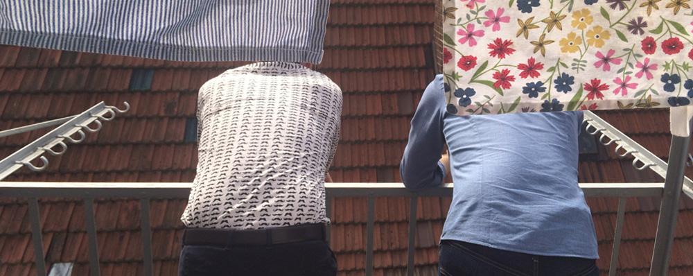 Zwei Männer unterhalten sich auf einem Balkon