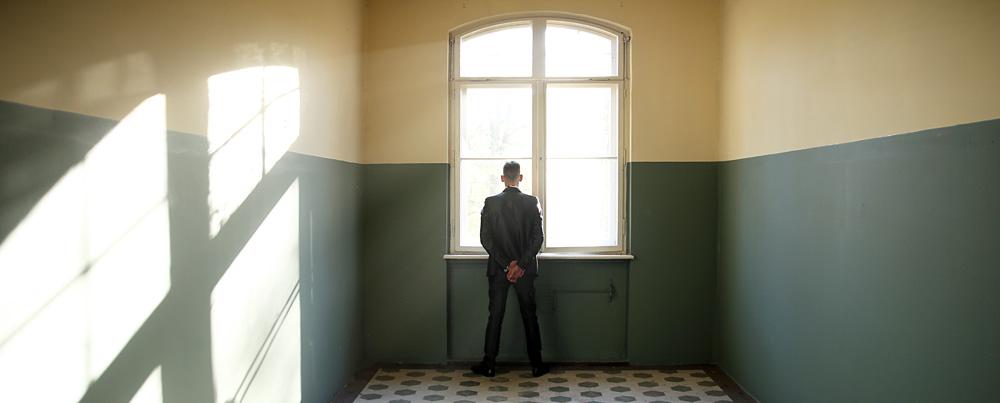 Mann am Fenster in einem leeren Raum