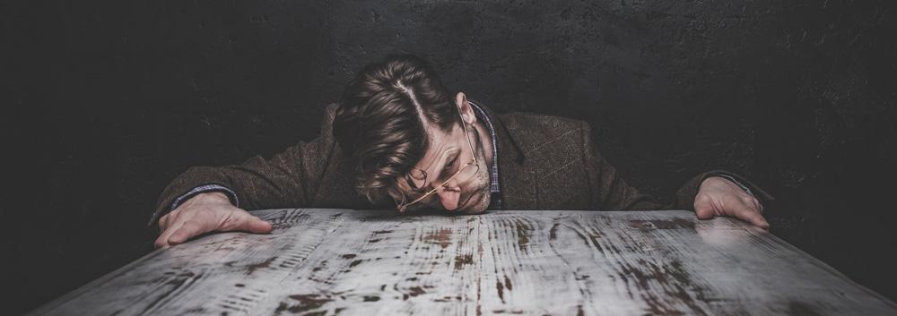 Ein Mann der müde am Tisch sitzt
