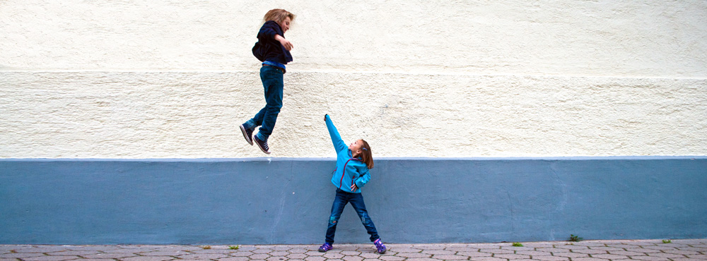 Junge und Mädchen spielen vor einer Wand