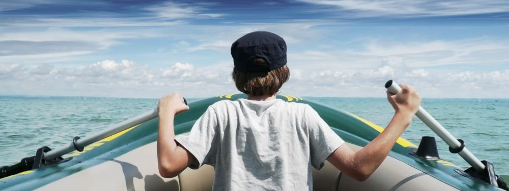Junge rudert in einem Schlauchboot