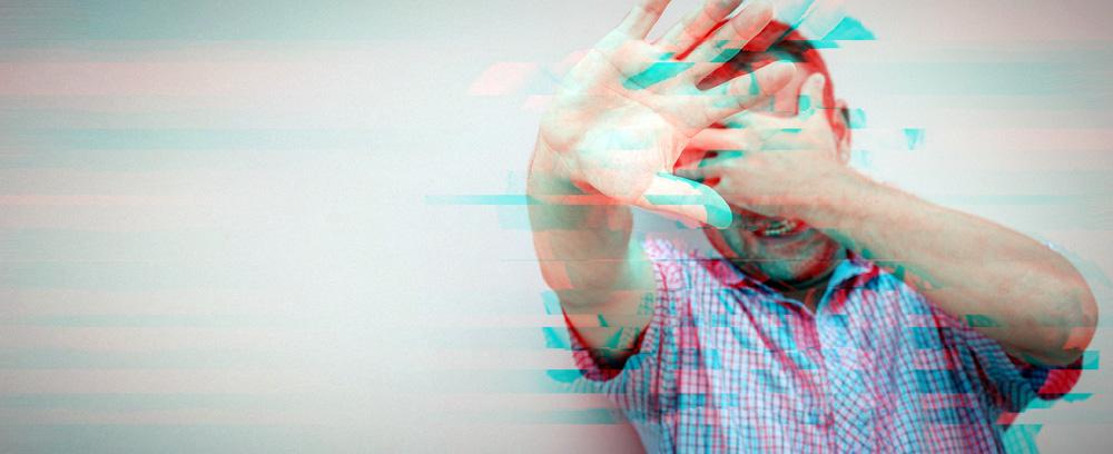 Mann hält sich die Hand vors Gesicht